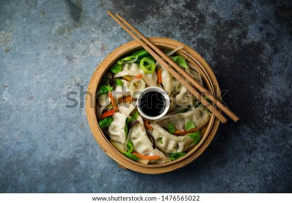 Asian steamed dumplings with vegetables in basket