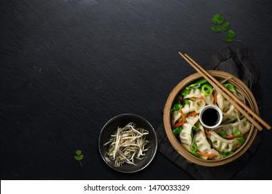 Asian steaming dumplings with vegetables in basket