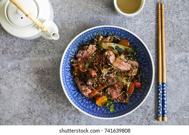Asian stir fry beef fillet with rice noodles, bok choi, zucchini, radishes and sesame seeds