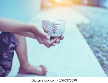 Asian street beggar child holding a cup asking for help and charity on concrete floor, Conceptual image , Society problem concept