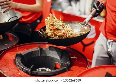 Asian street food festival in city. Chef cooking noodles and vegetables in a pan on fire. Fried chinese japanese noodles with vegetables and shrimps in wok on the open fire