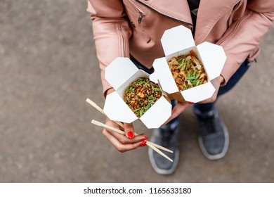 Asian street food: Japanese rice fried in sesame oil with egg, Teriyaki sauce, grilled chicken, fresh paprika, sesame, onions and green onions and yakisoba with grilled chicken in sauce.