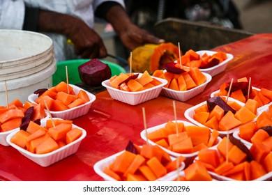 Asian street fruit mix chaat stall in market plate full of fresh healthy orange papaya, beet - image
