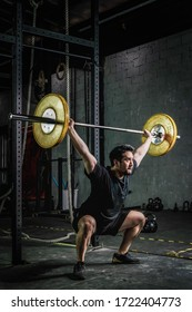 asian strong athletic man having workout and bodybuilding with barbells weight lift over head squat style in gym and fitness club in dark two tone