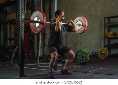 asian strong athletic man having workout and bodybuilding with barbells weight front squat setting style in gym and fitness club in dark tone