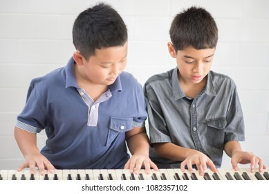 Asian student boys playing piano together in the class