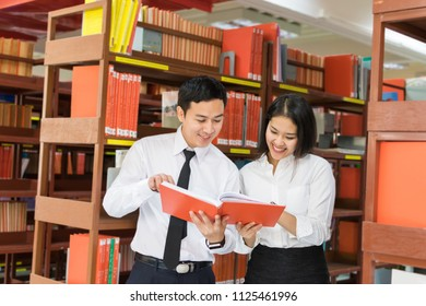 Asian student couple in uniform happy learning at the library in the university or college.