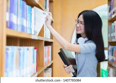 asian student getting books in a library.Woman taking book from library bookshelf. Young librarian searching books and taking one book from library bookshelf