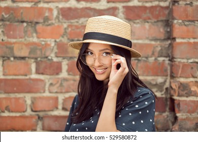 Asian student girl. Beautiful woman holding glasses against brick wall background. Mixed race student girl on university college campus park smiling happy and looking at camera.