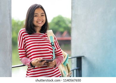 Asian student girl with a digital tablet in the park in a sunny summer day
