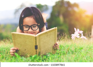 asian student girl with glasses lying on the grass reading a book in garden at summertime