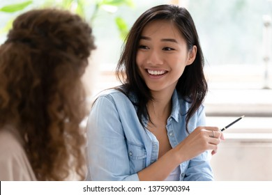 Asian student girl looking at group mate talking studying learn prepare for exam sitting in classroom, diverse friends employees working together on new project communicating discussing concept image