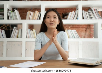 Asian student girl sit at desk in classroom or library films educational vlog or web-based seminar, woman record job interview tell about herself education knowledge level pretends to company position