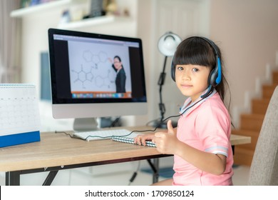 Asian  student girl video conference e-learning with teacher on computer and thumb up in living room at home. E-learning ,online ,education and internet social distancing