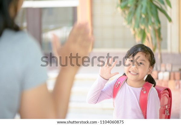 Asian student going to school and waving goodbye at school, back to school concept