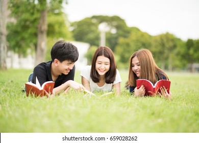 Asian student lie on grass and read books