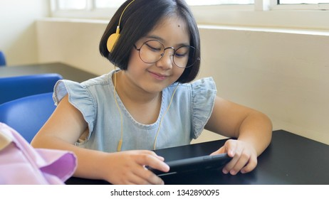 Asian student listening music by headphones in school library