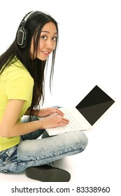 Asian student listening to music on the computer while studying isolated over a white background