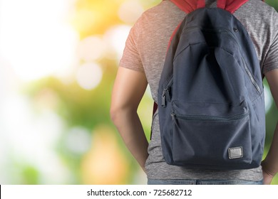 asian student man on gray t-shirt carry blue bag with bright nature background