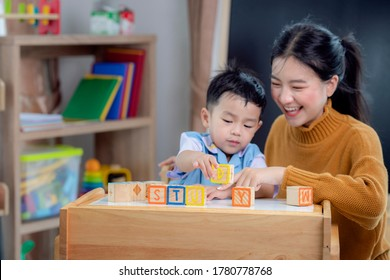 Asian student in preschool use a letter box make a study word in class room with his teacher, this image can use for genius, clever, education and school concept.