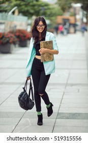 Asian student or school girl street portrait. Woman smiling and walking outside with backpack and book in casual business suite against blurred city space. Beautiful young mixed race Asian Caucasian