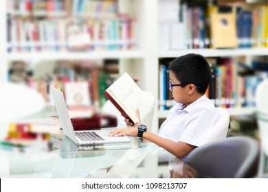 Asian student is searching for knowledge with book and laptop in the library.