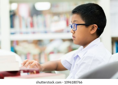 Asian student is searching for knowledge with laptop in the library.