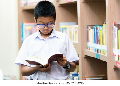 Asian student is searching for knowledge in the library.