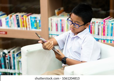 Asian student is searching for knowledge with tablet in the library.