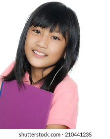 Asian student standing and smiling with book and headphones