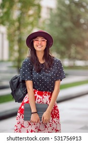 Asian student street style. Woman standing outside with backpack and tablet pc in casual look against blurred city space. Beautiful young mixed race Asian Caucasian woman looking at camera and smiling