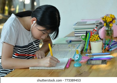 Asian student teenage girl studying alone by writing on notebook and making short notes about science of food and sugar molecule for exam or homework with school supplies and brown table background