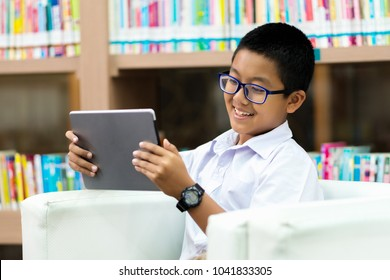 Asian student is watching movie on tablet in the library with happiness.