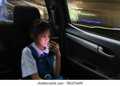 Asian students girl enjoy a phone on the personal cars while back home during the evening.