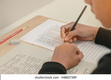 Asian Students holding pencil in hand doing multiple-choice quizzes or testing exams answer sheets exercises on old wood table In secondary school, college university classroom in education concept.