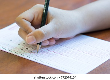 Asian Students holding pencil in hand doing multiple-choice quizzes or testing exams answer sheets exercises on old wood table. education concept