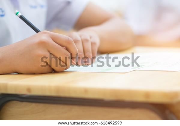 Estudantes asiáticos segurando lápis na mão fazendo testes de múltipla escolha ou testando exames fichas de resposta exercícios na velha mesa de madeira Na escola secundária, escola universitária universitária em conceito de educação