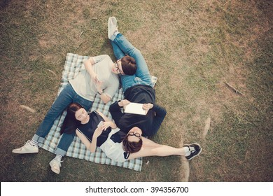 Asian students with mobile devices resting in the park, view from above