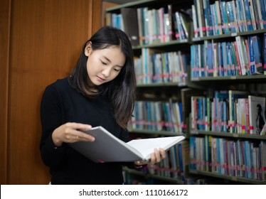 Asian students reading books in the library.