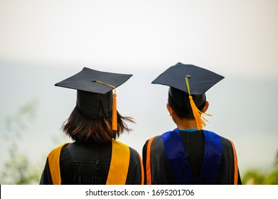 Asiatische Studenten trugen schwarze, feine Anzüge, schwarze Hüte, gelbe Tassels am Studientag.