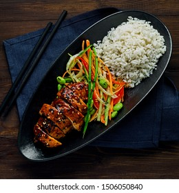 Asian- style chicken with savory and sweet teriyaki sauce, rice, sesame, salad, edamame and sweet chili sauce on a wooden table with a blue tablecloth. Top view, directly above.