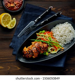 Asian- style chicken with savory and sweet teriyaki sauce, rice, sesame, salad, edamame, lemon and sweet chili sauce on a wooden table with navy tablecloth. Top view, directly above.