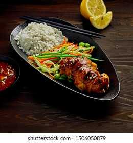 Asian- style chicken with savory and sweet teriyaki sauce, rice, sesame, salad, edamame, lemon and sweet chili sauce on a wooden table.