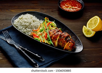Asian- style chicken with savory and sweet teriyaki sauce, rice, sesame, salad, edamame and sweet chili sauce on a wooden table.
