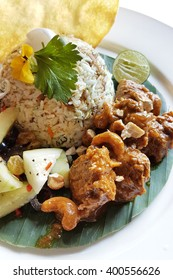 Asian style fried rice that's served with mutton curry, lime, cracker and some vegetable.
