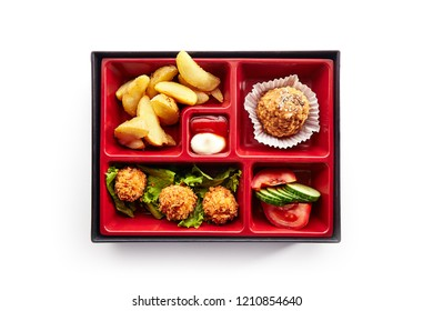 Asian Style Lunch Box with Deep Fried Balls, Salad, French Fries and Dessert Top View. Fresh Food Portion in Bento Box with Vegetables, Baked Potatoes, Meat in Breadcrumbs and Cake Isolated on White