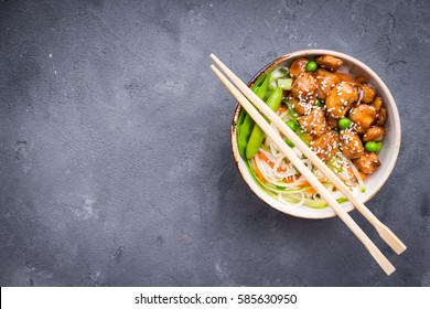 Asian style noodles with teriyaki chicken, vegetables and green peas pods. Noodles in bowl on rustic concrete background. Chinese/thai/japanese style stir fry noodles. Space for text. Top view
