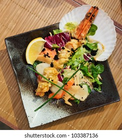 Asian style seafood dish on black plate