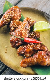 Asian Style Spicy Chicken Wings Appetizer with Lime and Hot Sesame, close-up