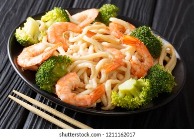Asian style udon noodles with shrimp, broccoli and soy sauce close-up on a plate on the table. horizontal